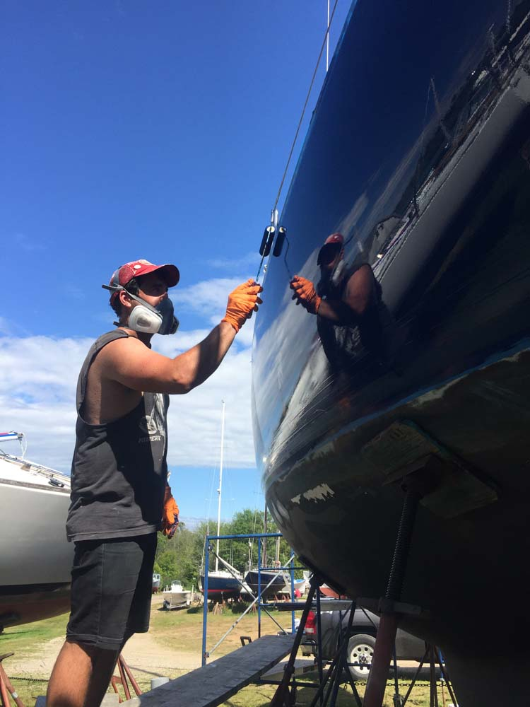 Painting the topsides with a foam roller - DIY in the Finestkind boatyard in Maine